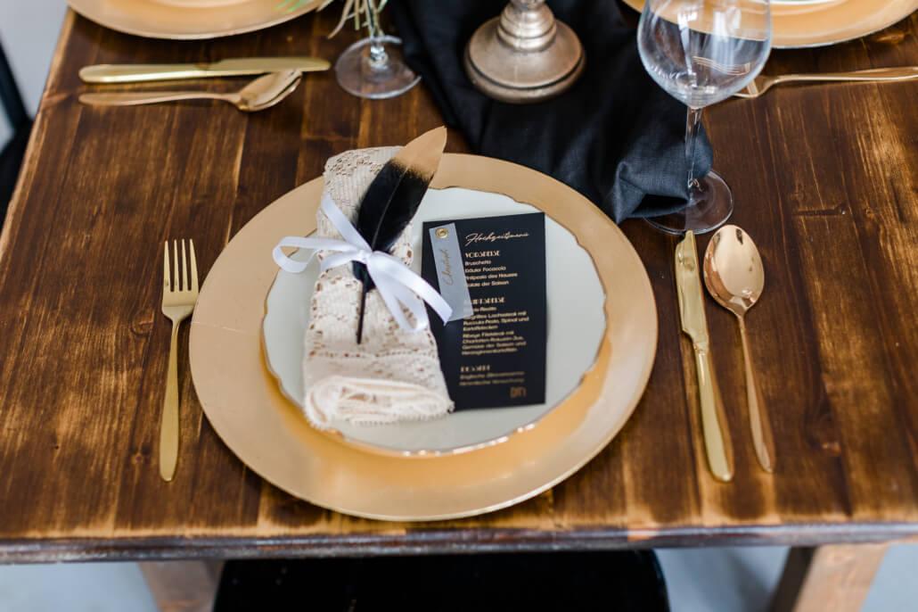 Tischdeko mit Menükarte auf Teller in schwarz gold Great Gatsby Hochzeit