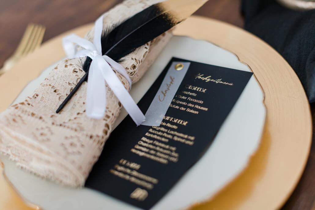 schwarz goldene Menükarte auf Teller liegend zum Hochzeitsthema Great Gatsby