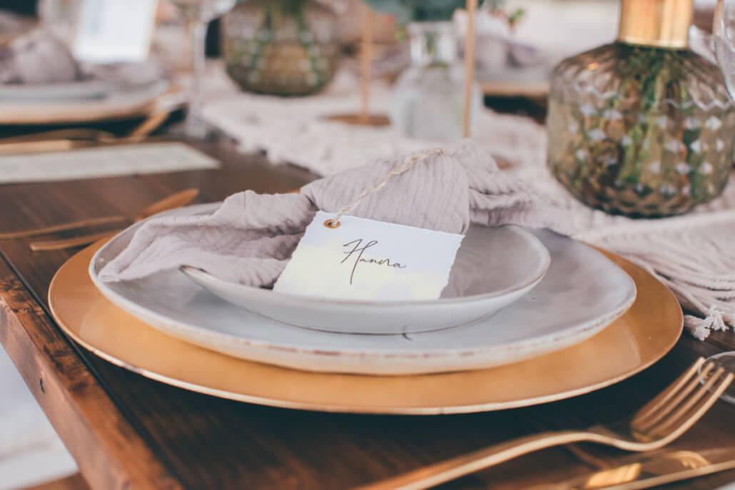 Platzteller gold mit 2 Speisetellern auf Holztisch mit goldenem Besteck und Musselin Serviette mit Namenskärtchen