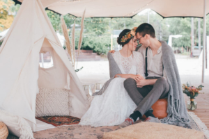 Brautpaar kuschelt in Boho Lounge mit Tipi-Zelt