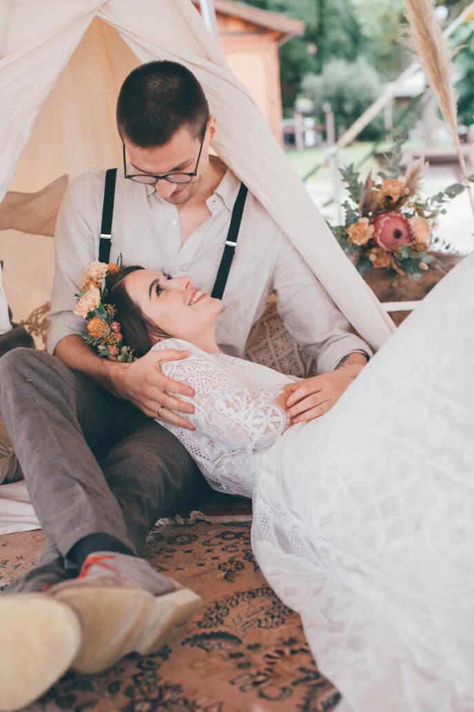Brautpaar kuschelt in Boho Lounge