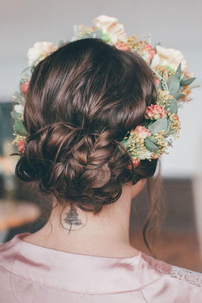 Braut von hinten beim Getting Ready mit lockerer Hochsteckfrisur und Blumenkranz
