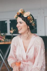 lachende Braut beim Getting Ready mit Blumenkranz und Morgenmantel
