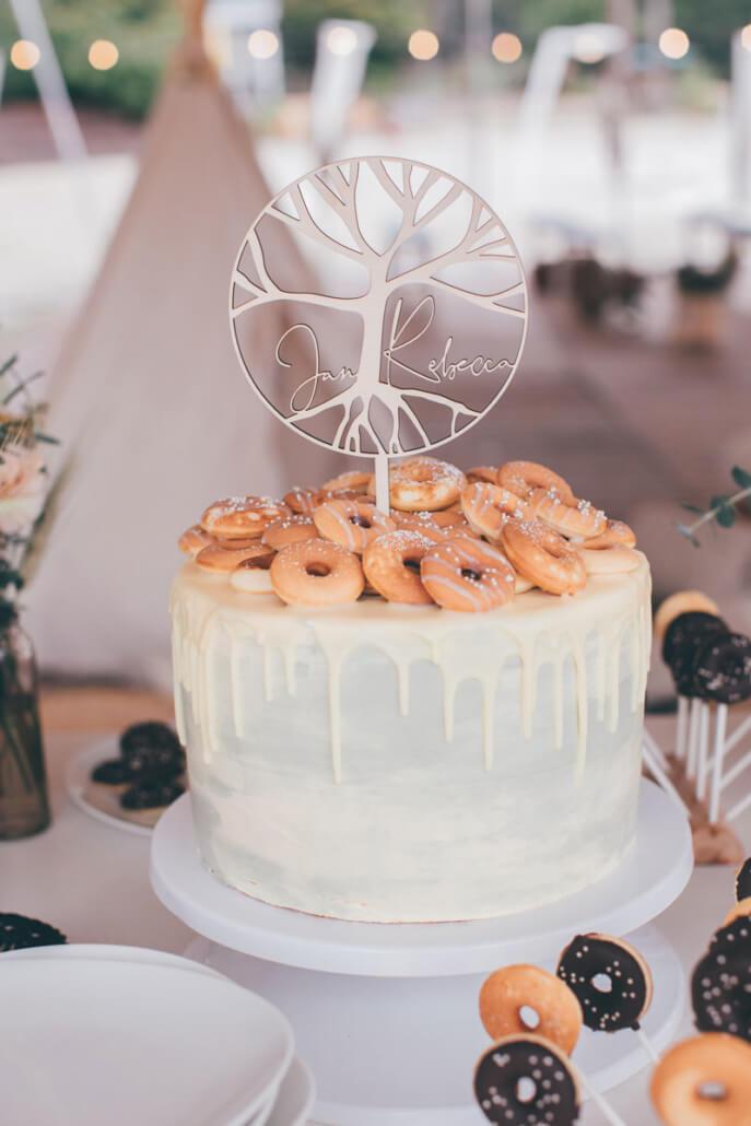 Hochzeitstorte Dripping Cake in olivgrün und gelb mit Mini-Donuts und Holz-Caketopper Hochzeitslogo