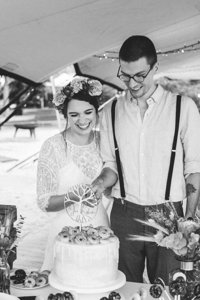 lachendes Brautpaar schneidet Hochzeittorte an
