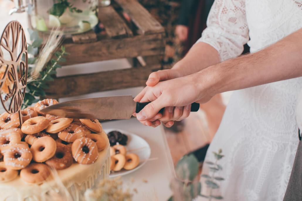 Tortenanschnitt der Hochzeitstorte mit Mini-Donuts