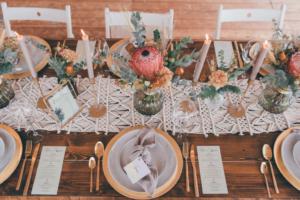 Holztisch mit Makramee Tischläufer, goldenen Platztellern, Protea und Eukalyptus