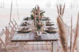 Tischdekoration für eine Strandhochzeit mit Stabkerzen, Pampasgras, Eukalyptus und Makrameetischläufer