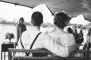 Brautpaar von hinten sitzend auf einer Holzbank mit Traurednerin unter einem Zelt
