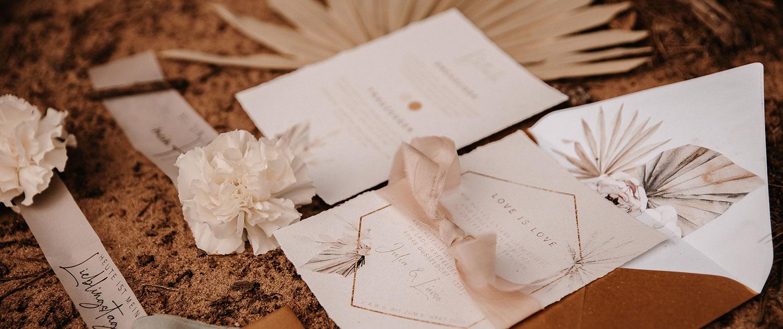 Flatlay Detail der Einladung für gleichgeschlechtliches Paar mit Trockenblumen und Seidenband in Blush