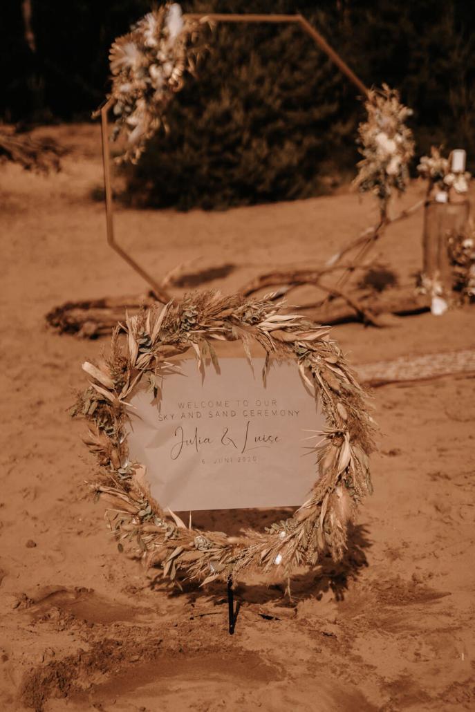 Willkommensschild vor Boho-Traubogen einer Hochzeit