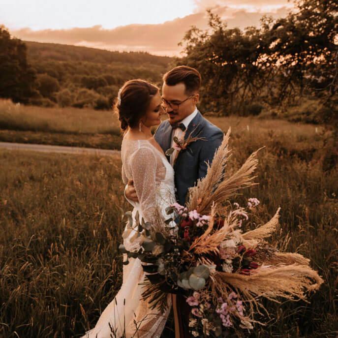 Brautpaarshooting mit üppigem Brautstrauß im Feld im Sonnenuntergang