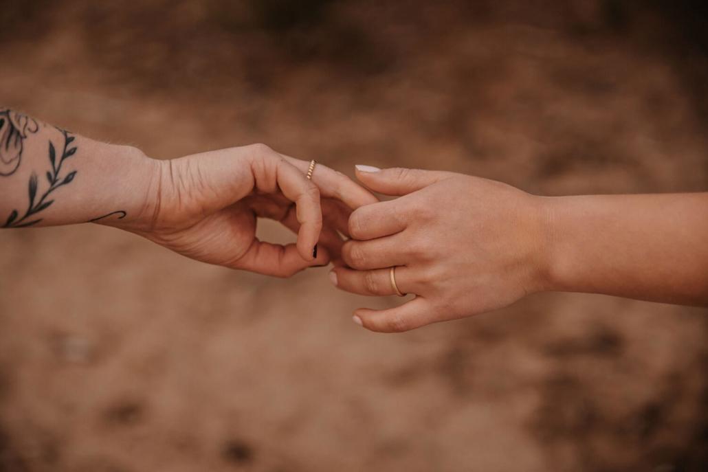 Eheringe in Gold. Brautpaar fasst sich an den Händen