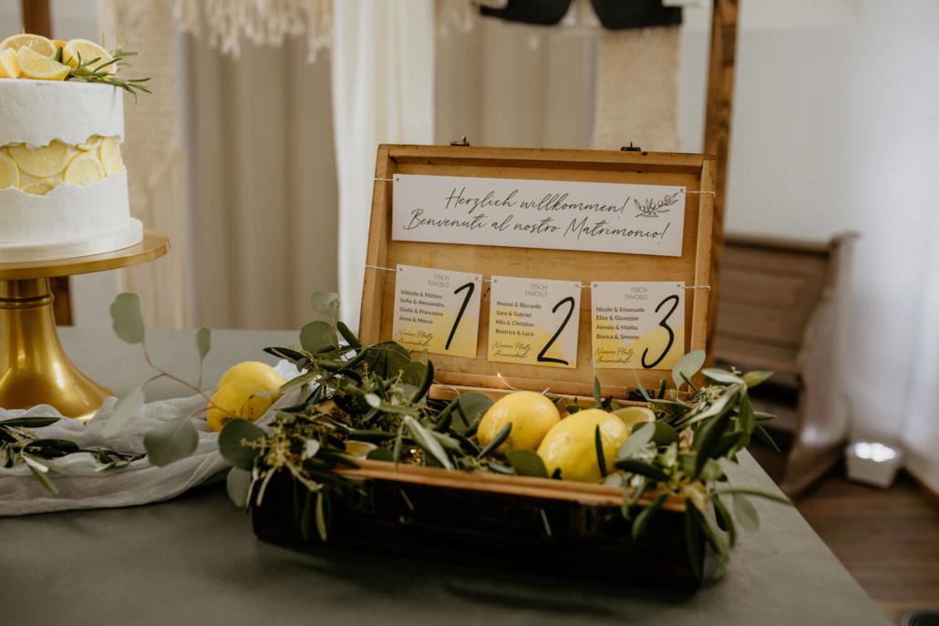 Sitzplan für eine Tiny Wedding in altem Holzkoffer mit Olivenzweigen und Zitronen dekoriert